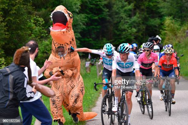 A man dressed with a dinosaur costume runs next to riders Britain's rider of team Sky Christopher Froome and Britain's rider of team MitcheltonScott...