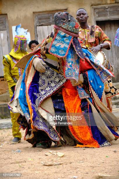 Man dressed with an Egungun mask performing during a ritual dance The Egungun is a Yoruba character that represents the ancestors in the religious...