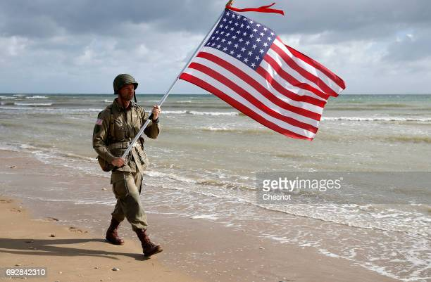 A man dressed with US 101st airborne division military uniforms with an American Stars and Stripes flag walks on the beach during commemorations...