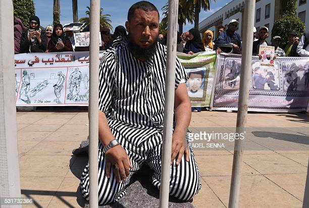 A man dressedup as a prisoner performs as supporters of Moroccan Salafist prisoners protest on May 16 2016 outside the parliament in Rabat to demand...