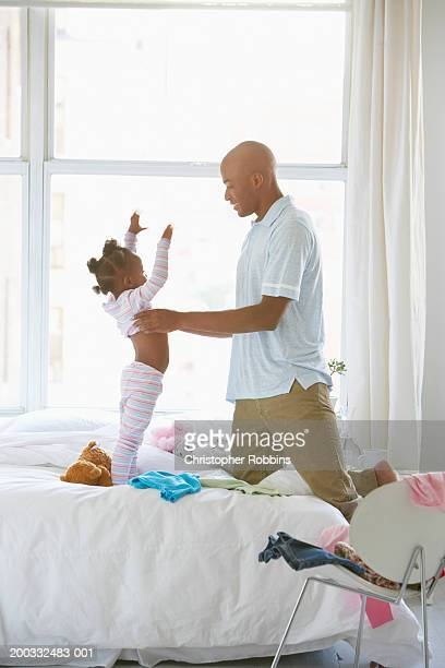 man dressing daughter (2-4) in pyjamas - little girl taking off clothes stock photos and pictures