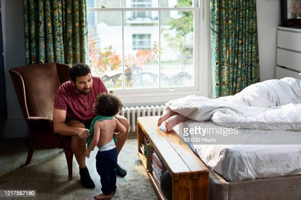 man dressing young son in bedroom - genderblend stock pictures, royalty-free photos & images
