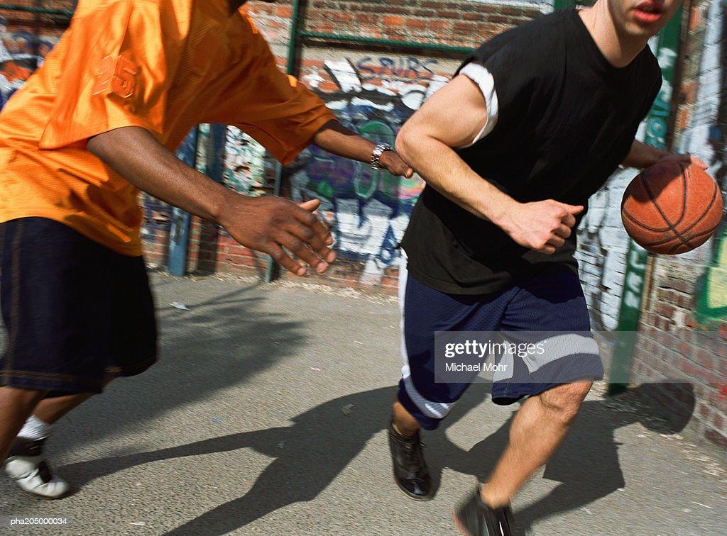 Man dribbling basketball against opponent next to graffiti wall : Stockfoto
