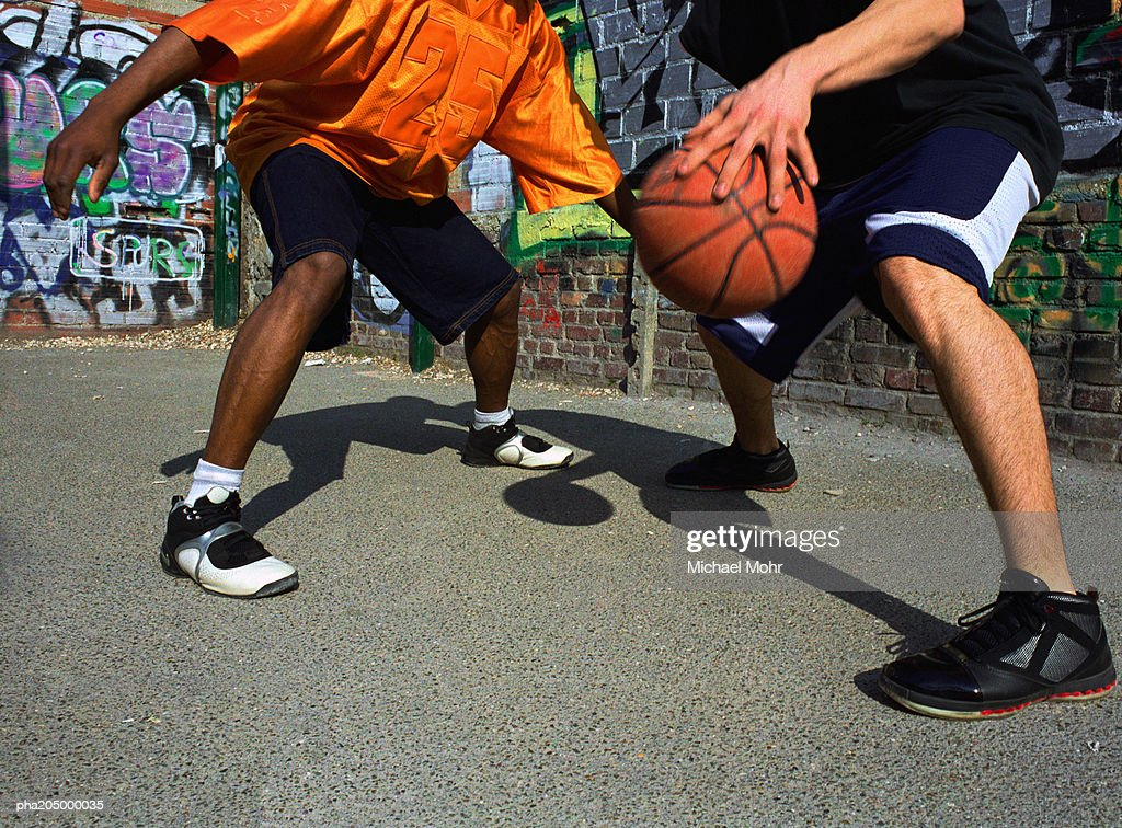 Man dribbling basketball against opponent next to graffiti wall : Stockfoto