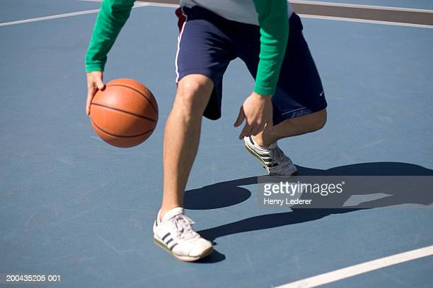 Man dribbling basketball, low section