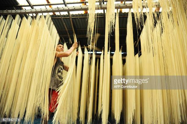 A man dries handmade 'long life' salty noodles in Singkawang West Kalimantan province on August 8 2017 The noodles which measure about two meters...