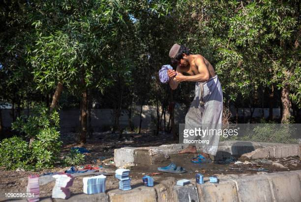 A man dries his clothes after washing them using water from a water pipe leakage in Karachi Pakistan on Monday Dec 24 2018 Women and children walk...