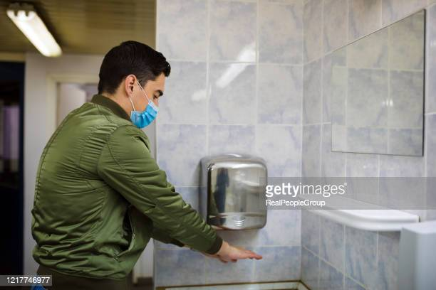 man dries wet hands with an electric hand dryers - public restroom stock pictures, royalty-free photos & images