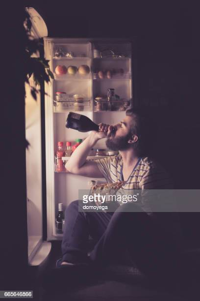 Man driking wine and eating pizza in front of the refrigerator during the night