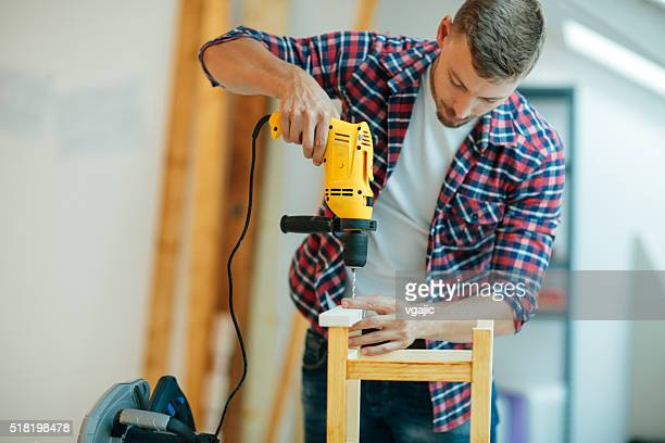 man drilling a plank. - drill stock pictures, royalty-free photos & images