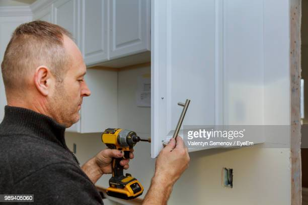 Man Drilling Cabinet At Home