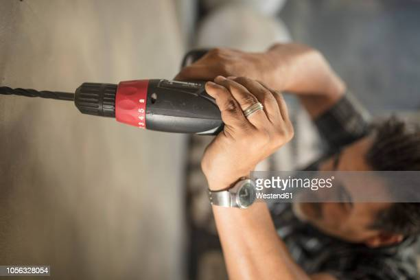 man drilling into wall, close-up - drill stock pictures, royalty-free photos & images