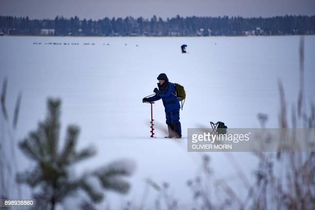 A man drills a hole while icefishing at midday on the barely frozen Bothnia Sea on December 27 2017 in Vaasa Western Finland The ice is only 10cm...