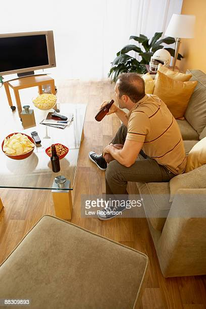 Man drinking a beer while watching television