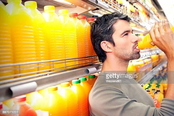 Man drinking a bottle of orange juice in front of fridge in a supermarket
