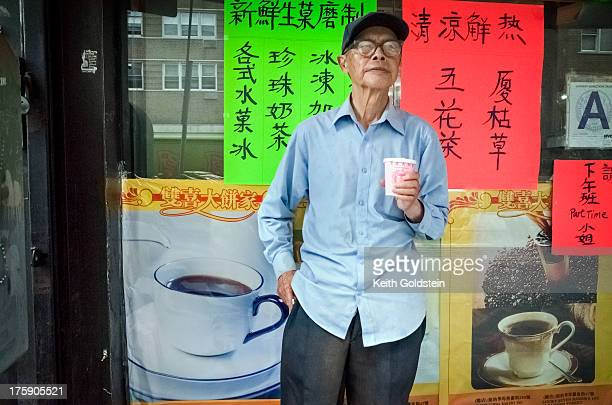 Man drinking a cup of coffee in front of a bakery in Chinatown, New York City.