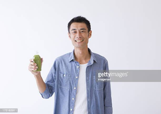 Man drinking a glass of green juice