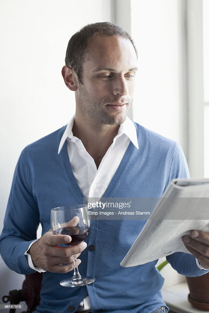 A man drinking a glass of wine and reading a magazine : Stock Photo