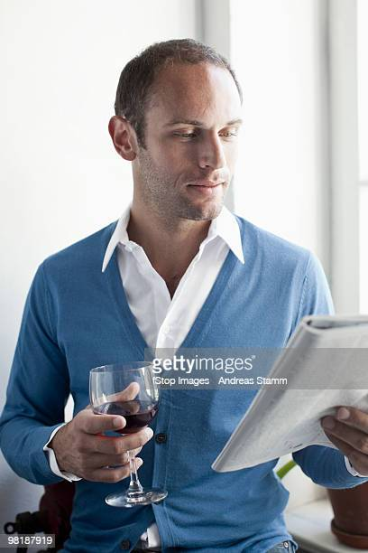 A man drinking a glass of wine and reading a magazine