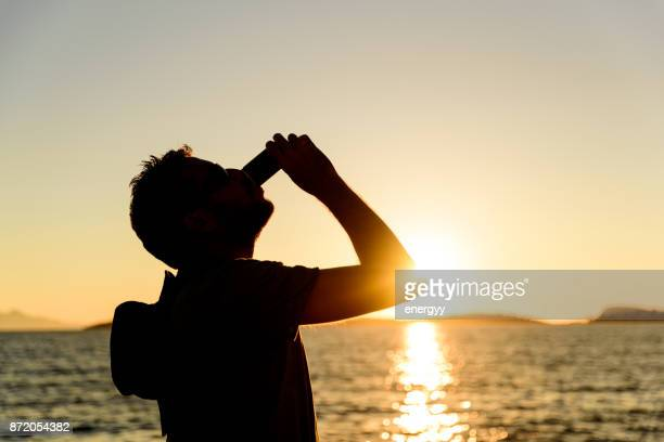 hombre bebiendo un refresco - coca cola fotografías e imágenes de stock