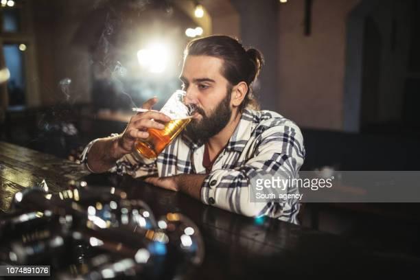hombre bebiendo sola - alcoholismo fotografías e imágenes de stock