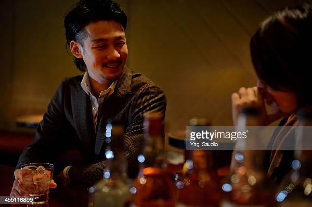 Man drinking at the bar and women