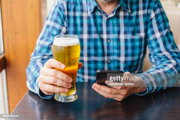 man drinking beer and using mobile phone in a bar - ビアグラス ストックフォトと画像