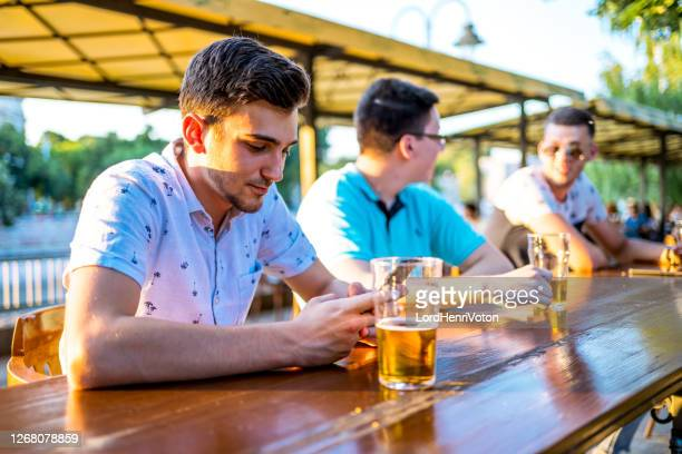 man drinking beer and using mobile phone - phone message stock pictures, royalty-free photos & images