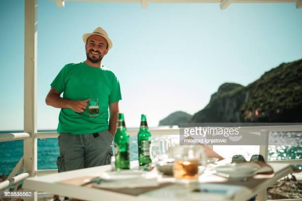 Man Drinking Beer at Sea Restaurant