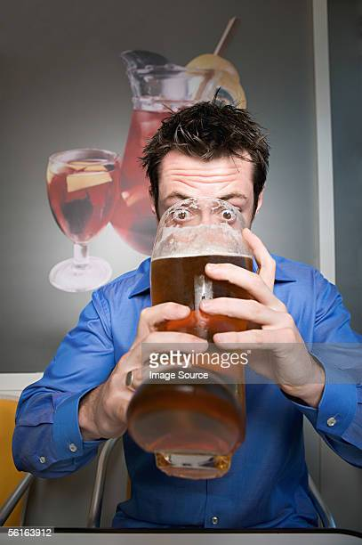 Man drinking beer from glass boot
