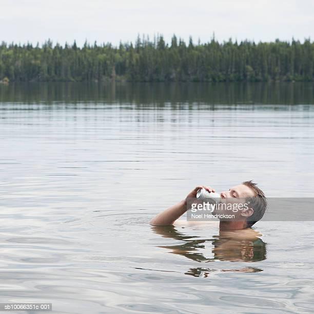 Man drinking beer in lake, side view