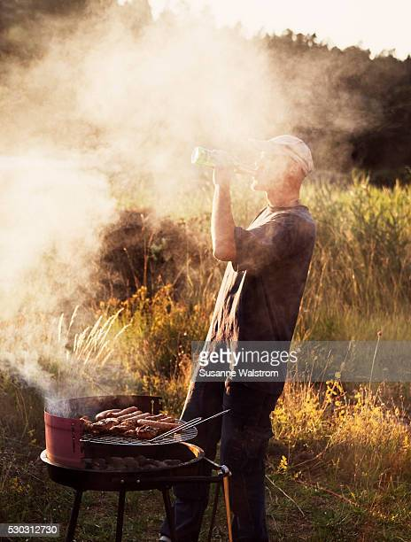 Man drinking beer next to barbecue grill