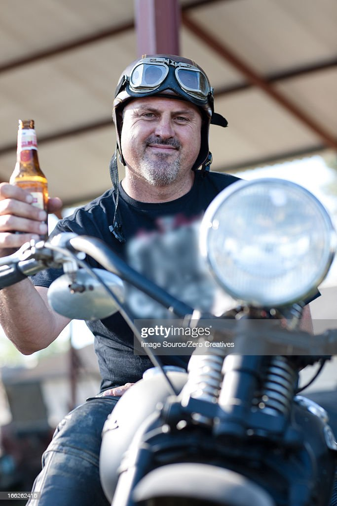 Man drinking beer on motorcycle : Stock Photo