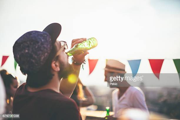 Man drinking beer on party with friends