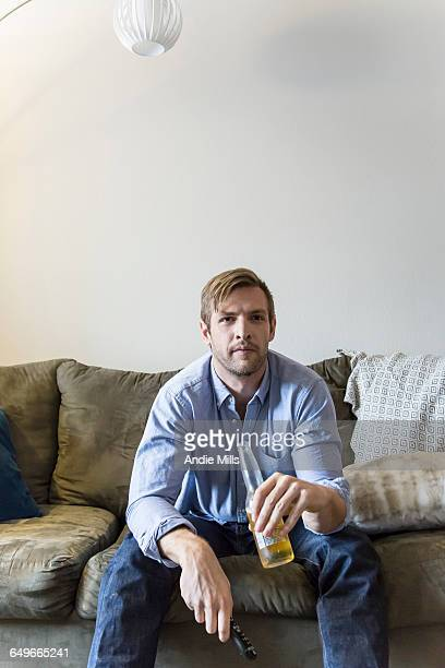 Man drinking beer on sofa