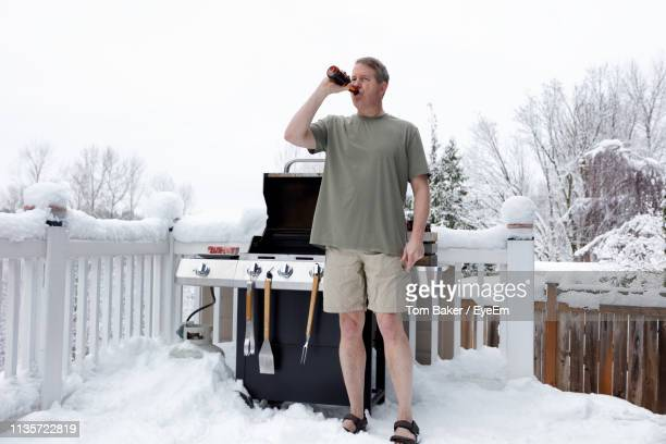 man drinking beer standing by barbecue grill during winter - shorts stock-fotos und bilder