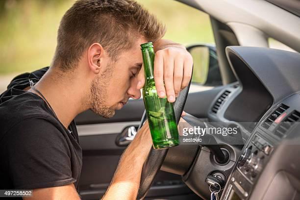 Hombre bebiendo cerveza mientras conducir un coche