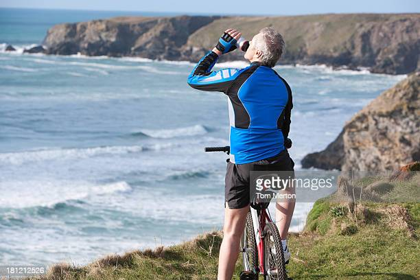 man drinking bottled water sitting on his bicycle