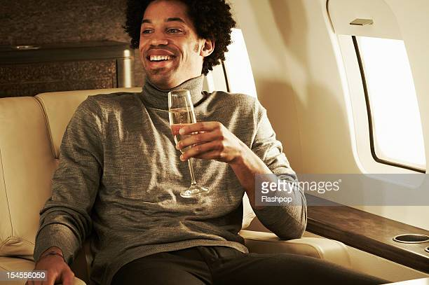 Man drinking champagne on private jet