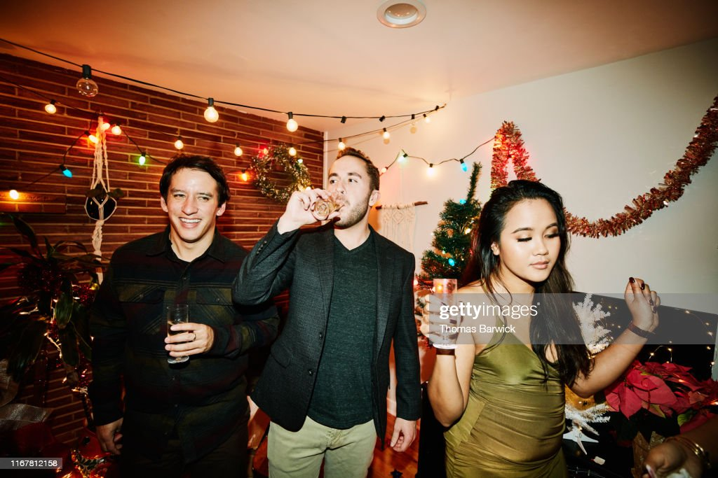 Man drinking champagne while hanging out with friends during holiday party : Stock Photo