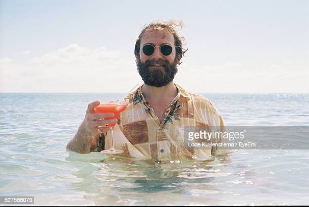 Man Drinking Cocktail In Sea
