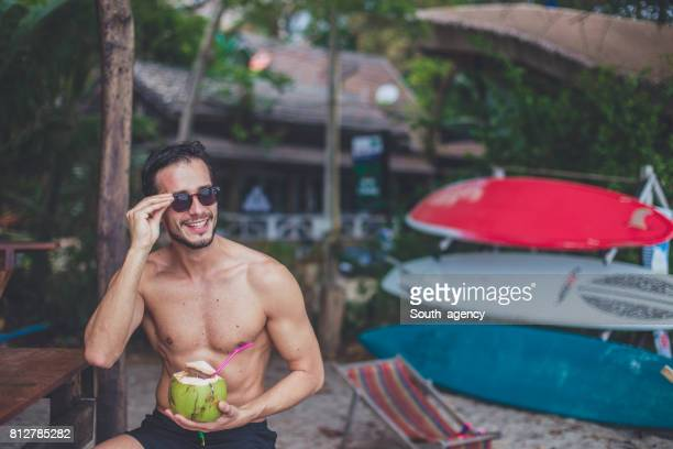 man drinking coconut cocktail on beach - coconut water stock pictures, royalty-free photos & images