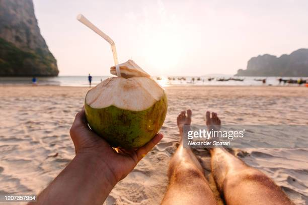 man drinking coconut from personal perspective at the beach at sunset - railay strand stock-fotos und bilder