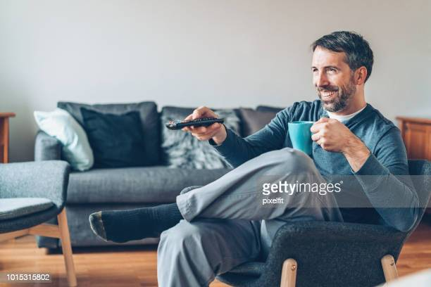 man drinking coffee and watching tv - changing channels stock photos and pictures