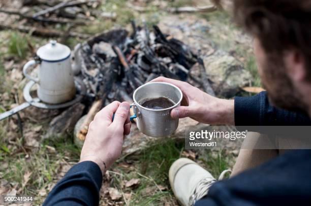 man drinking coffee at campfire - 薪 ストックフォトと画像