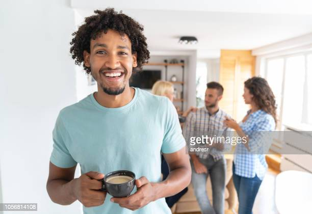 Man drinking coffee at home with a group of flat mates