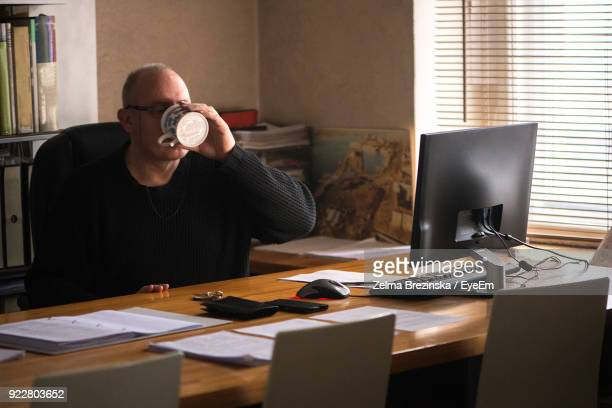 Man Drinking Coffee At Table In Office