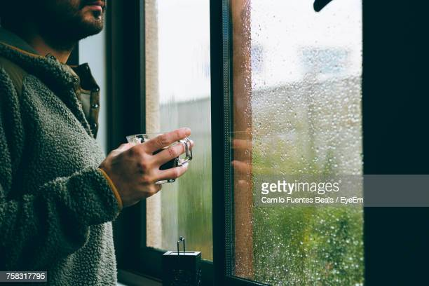 man drinking coffee at window - rain stockfoto's en -beelden