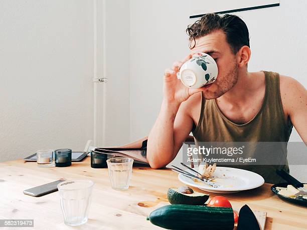 Man Drinking Coffee By Messy Table