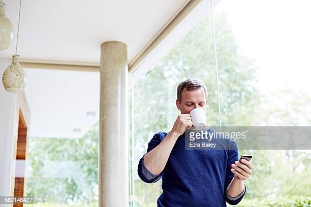 Man drinking coffee checking his phone